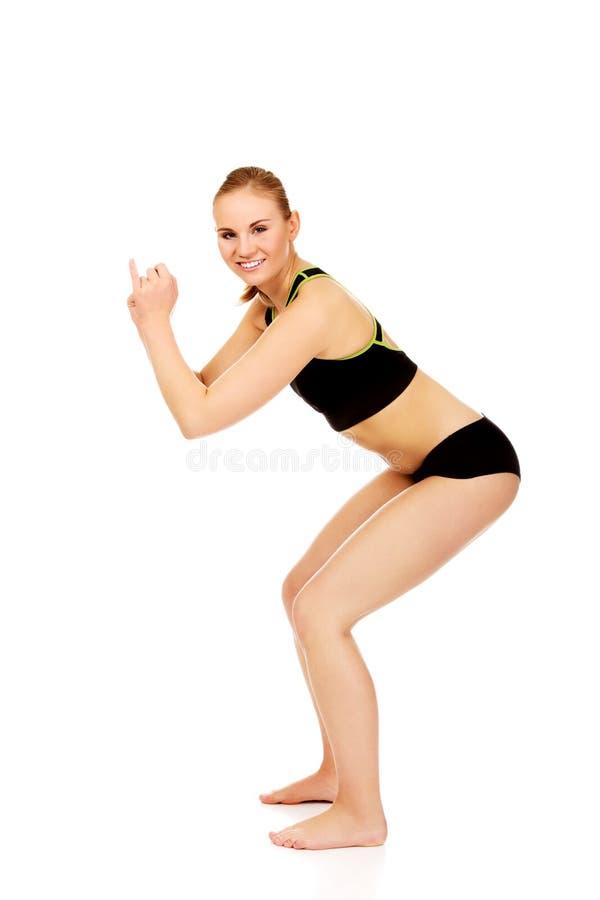 Молодая атлетическая женщина выполняет сидения на корточках стоковое изображение