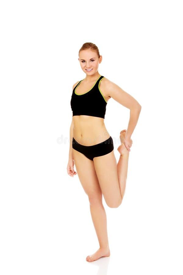 Молодая атлетическая женщина протягивая ее ногу стоковые изображения rf