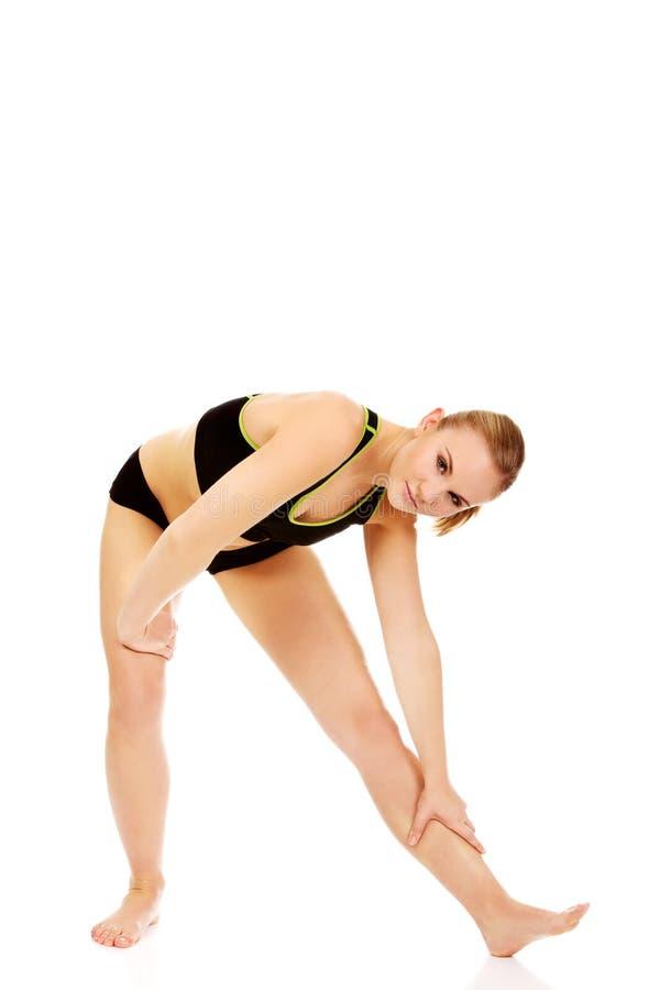 Молодая атлетическая женщина разрабатывая гимнастические тренировки стоковая фотография