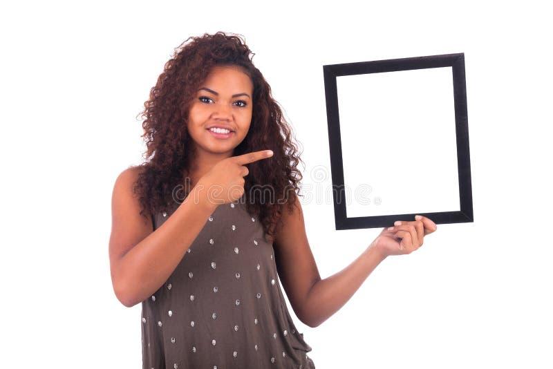 Молодая африканская женщина с рамкой вокруг ее стороны изолированной над a стоковое изображение