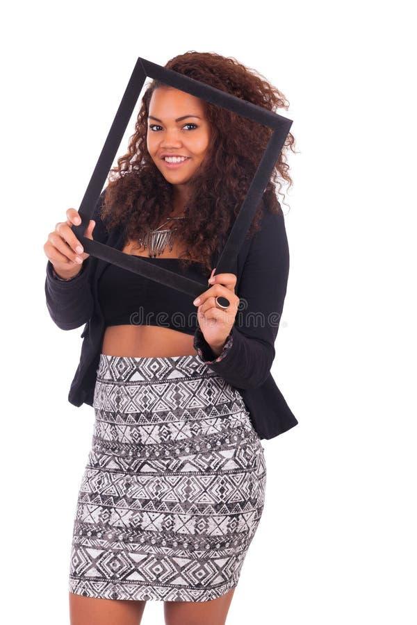 Молодая африканская женщина с рамкой вокруг ее стороны изолированной над a стоковые фотографии rf