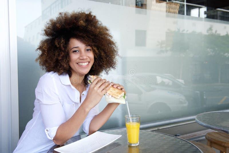Молодая Афро-американская женщина держа сандвич на кафе стоковые фотографии rf
