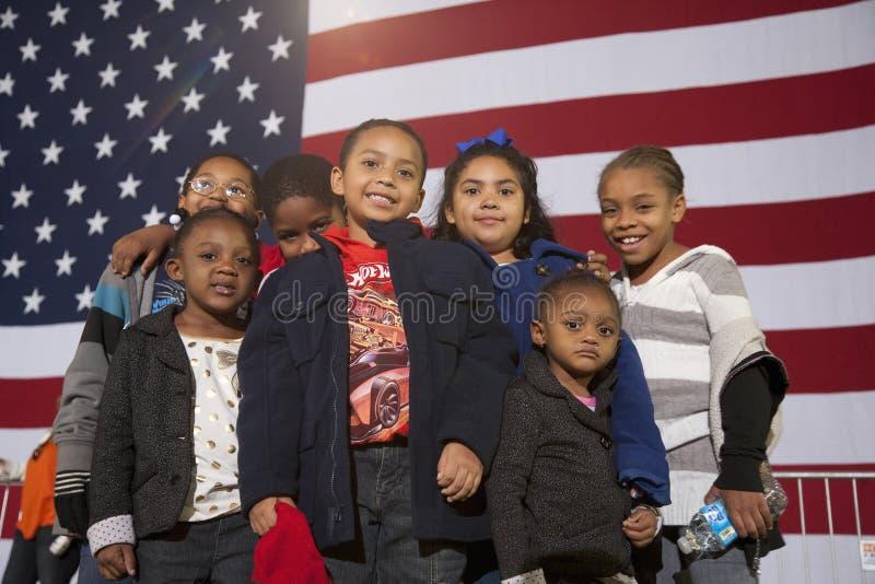 Молодая Афро-американская стойка детей перед американским флагом стоковые изображения rf