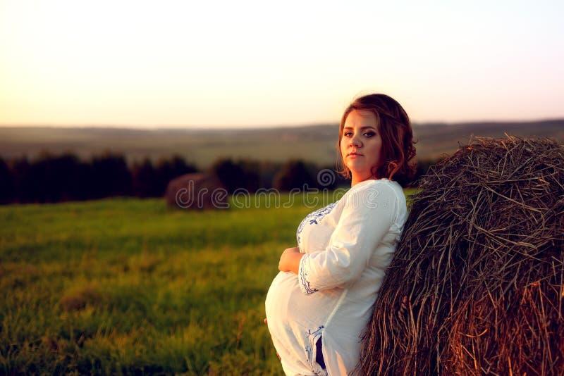 Молодая беременная женщина готовя стог сена на заходе солнца и Embr стоковое фото rf