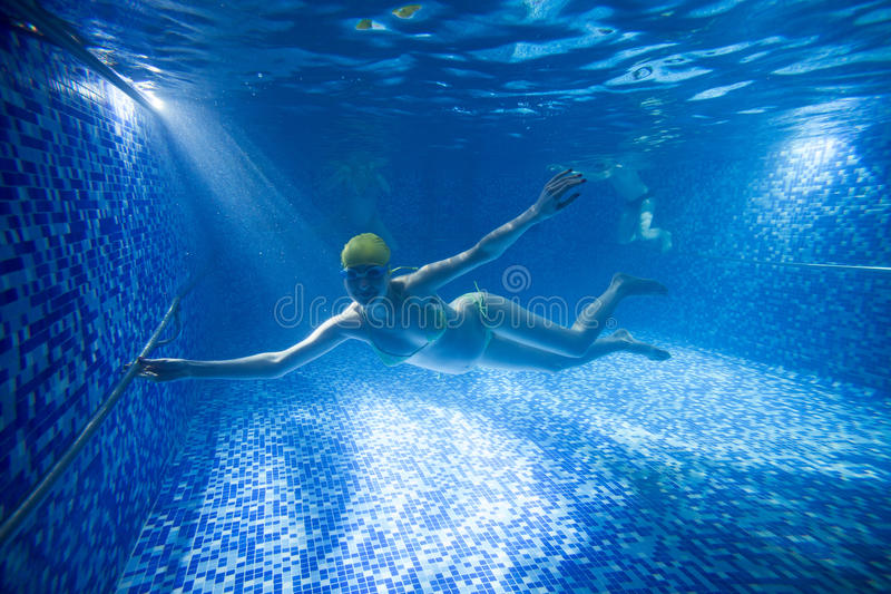 Молодая беременная женщина подводная в плавательном бассеине стоковые изображения