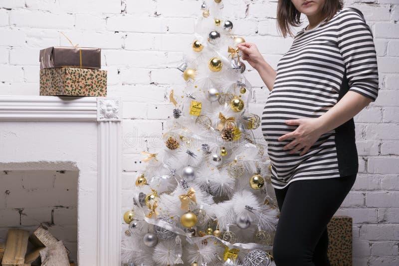 Молодая беременная женщина при подарочная коробка представляя на предпосылке рождественской елки стоковая фотография rf