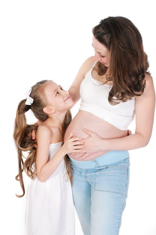 Молодая беременная женщина с ее дочерью на белом ба стоковые фото