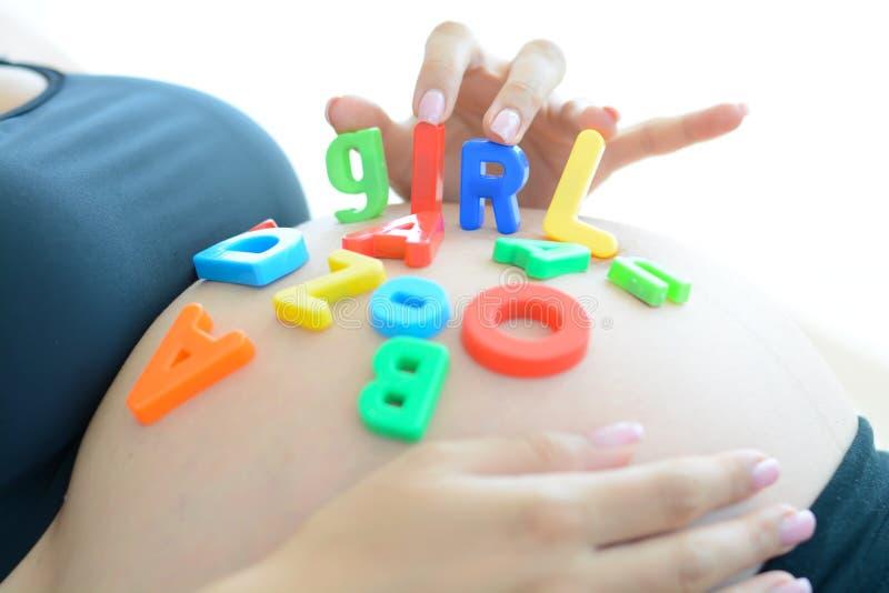 Молодая беременная женщина с письмом преграждает девушку правописания на ее беременном животе стоковая фотография rf