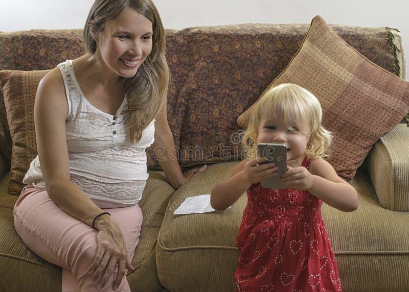 Молодая беременная мать смотря дочь оплачивая с cellul стоковая фотография