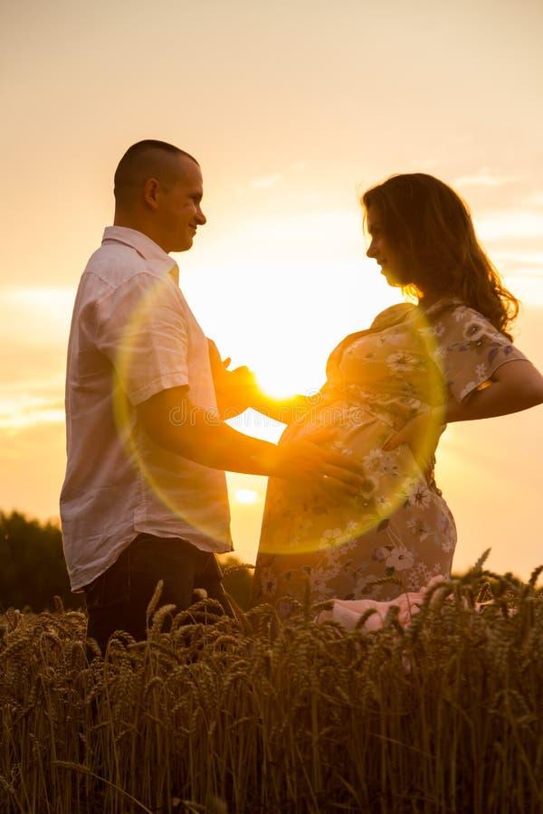 Молодая беременная пара в пшеничном поле стоковая фотография rf