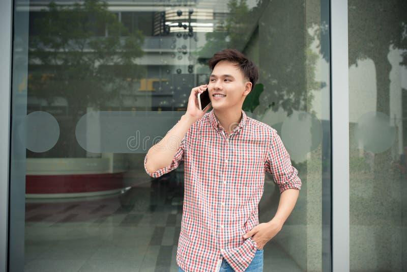 Молодая беседа бизнесмена к мобильному телефону в офисе стоковое изображение rf