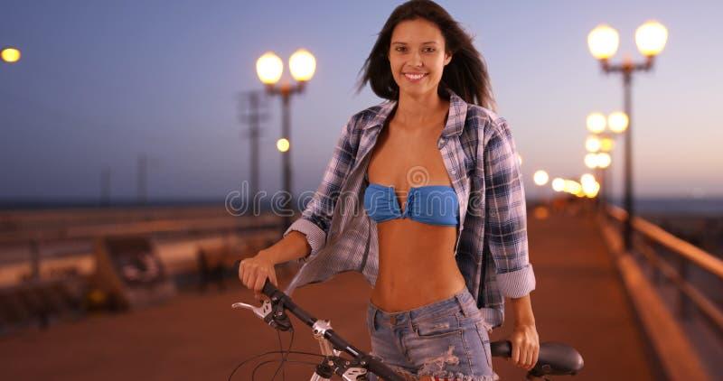 Молодая белая женщина представляет для портрета пока едущ ее велосипед на пристани стоковые фото