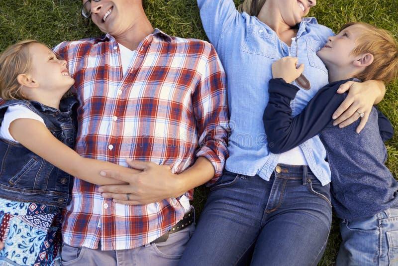 Молодая белая семья лежа на траве обнимая, съемке урожая стоковая фотография rf