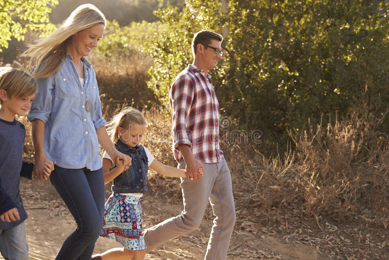 Молодая белая семья идя на путь в солнечном свете, взгляде со стороны стоковое фото rf