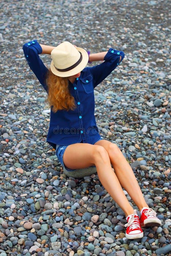 Молодая белокурая девушка в шляпе на пляже стоковая фотография