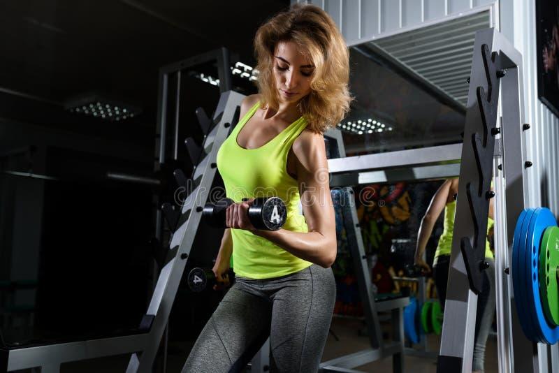 Молодая белокурая девушка делая тренировку с гантелями в спортзале стоковая фотография rf