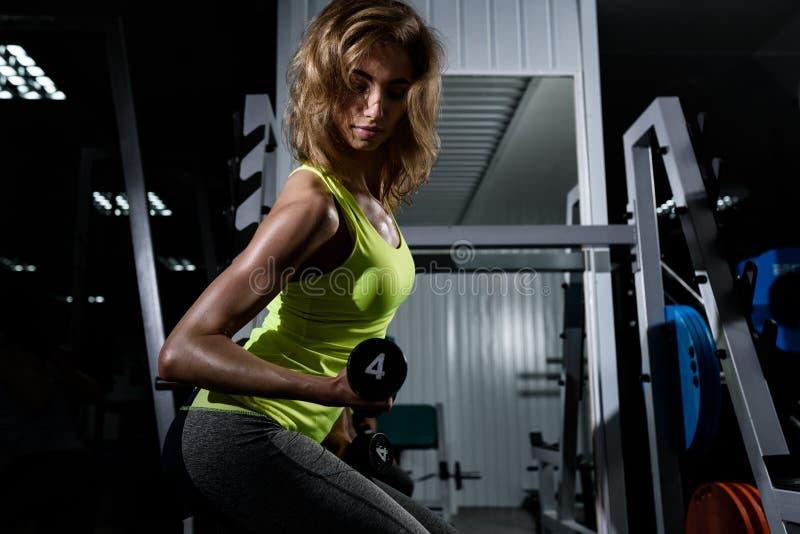 Молодая белокурая девушка делая тренировку с гантелями в спортзале стоковое фото rf