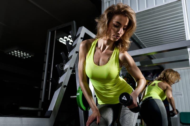 Молодая белокурая девушка делая тренировку с гантелями в спортзале стоковые фотографии rf