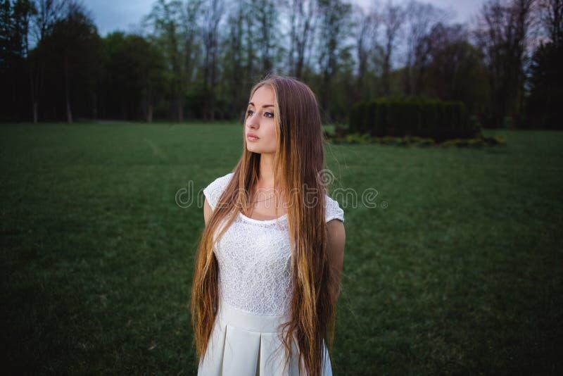 Молодая белокурая девушка загоренная волшебным фонариком в саде тайны ночи стоковые изображения