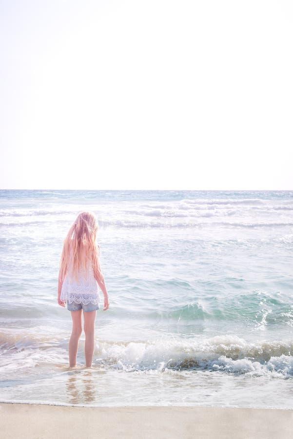 Молодая белокурая девушка стоя на пляже стоковые фотографии rf