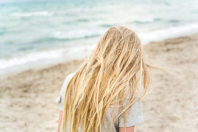 Молодая белокурая девушка стоя на пляже стоковое фото rf