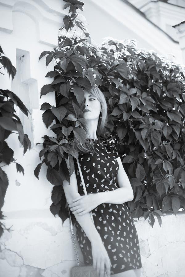 Молодая белокурая девушка стоя около стены листьев стоковая фотография rf
