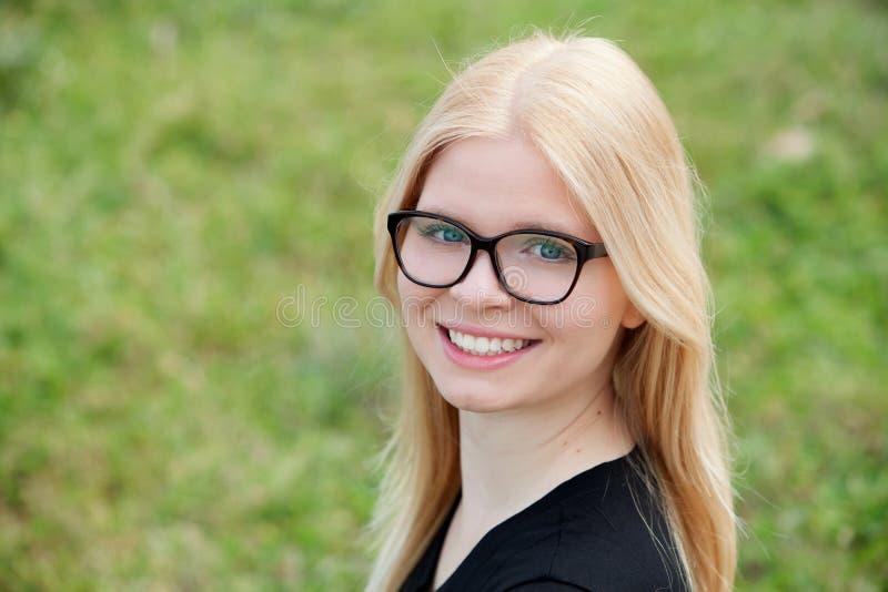 Молодая белокурая девушка с усмехаться стекел стоковое фото