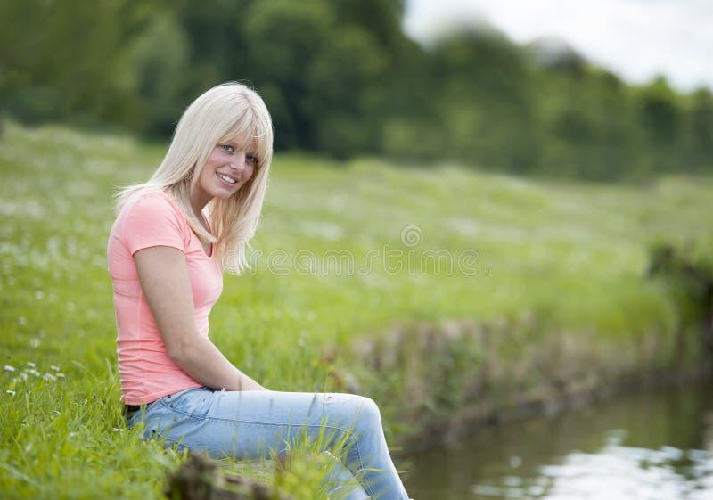 Молодая белокурая женщина в белизне усаженная на озеро стоковая фотография rf