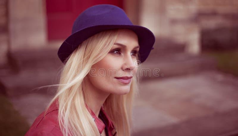 Молодая белокурая женщина в ультрамодной шляпе стоковое фото rf