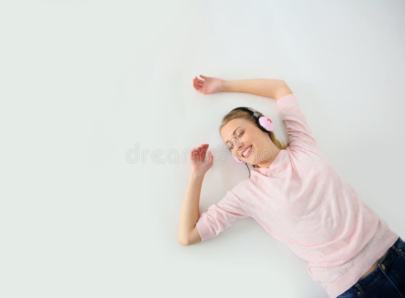 Молодая белокурая женщина лежа на музыке пола слушая стоковое изображение rf