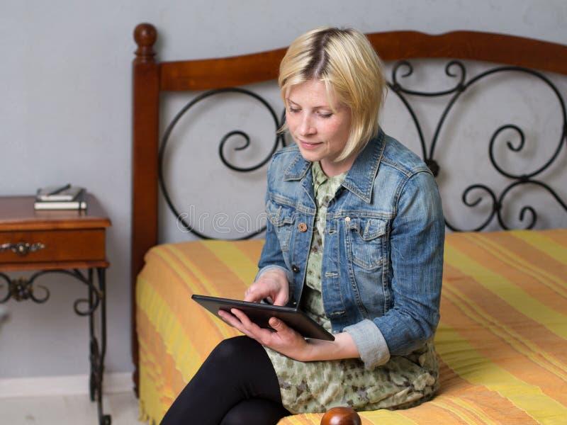 Молодая белокурая женщина держа таблетку и смотря экран стоковые фото