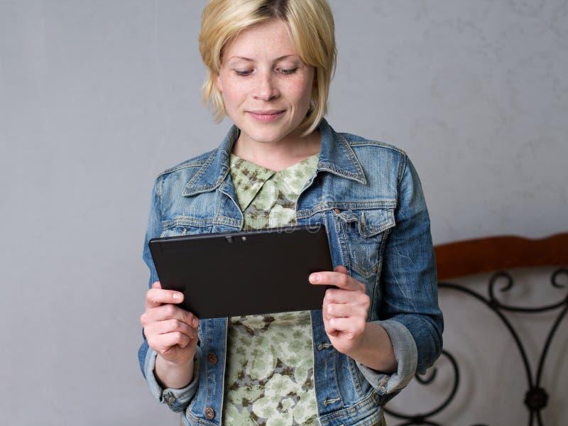 Молодая белокурая женщина держа таблетку и усмехаться стоковая фотография rf
