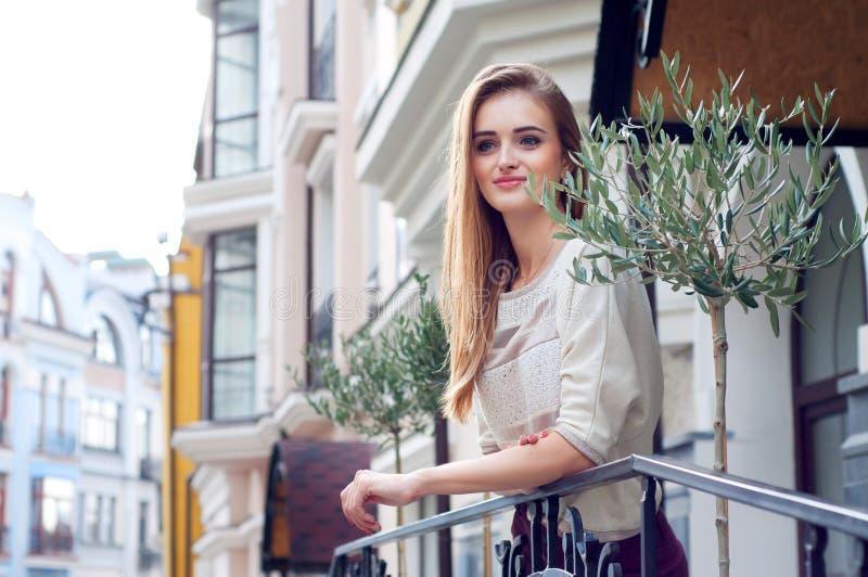 Молодая белокурая женщина на ее усмехаться балкона стоковое изображение rf