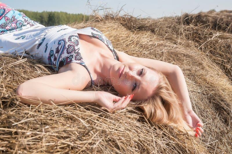 Молодая белокурая женщина на сене стоковое изображение