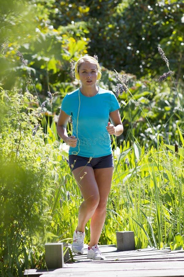Молодая белокурая женщина при музыка бежать в зеленой естественной предпосылке стоковое изображение rf