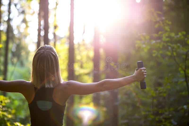 Молодая белокурая женщина разрабатывая с гантелями в красивом natur стоковое изображение