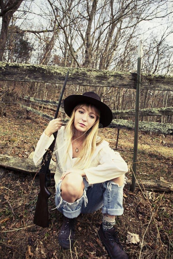 Молодая белокурая женщина распологая в древесины с оружием стоковые фото