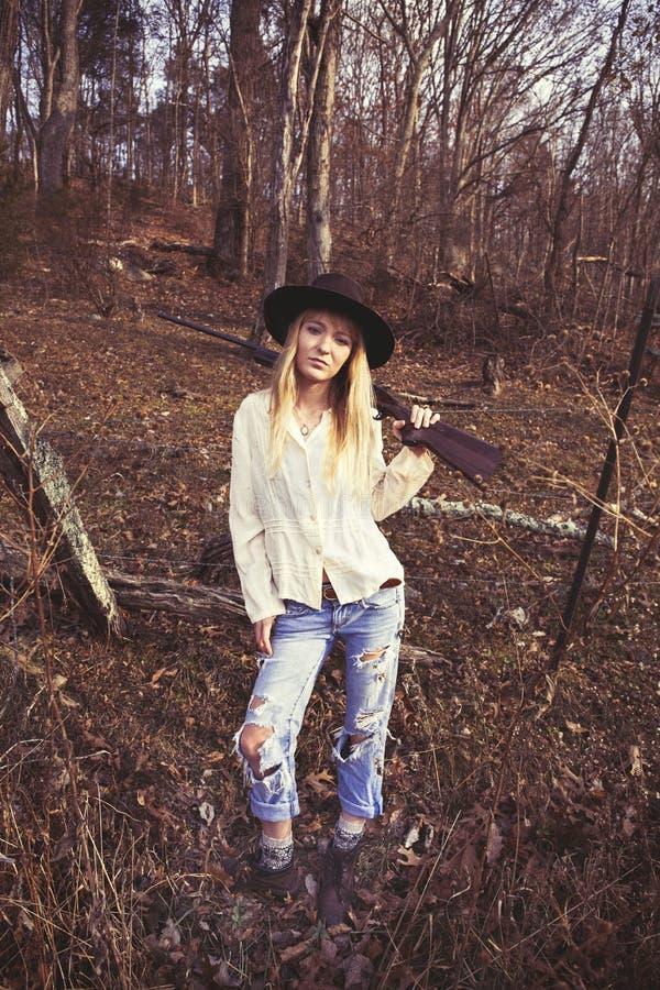 Молодая белокурая женщина распологая в древесины с оружием стоковое фото