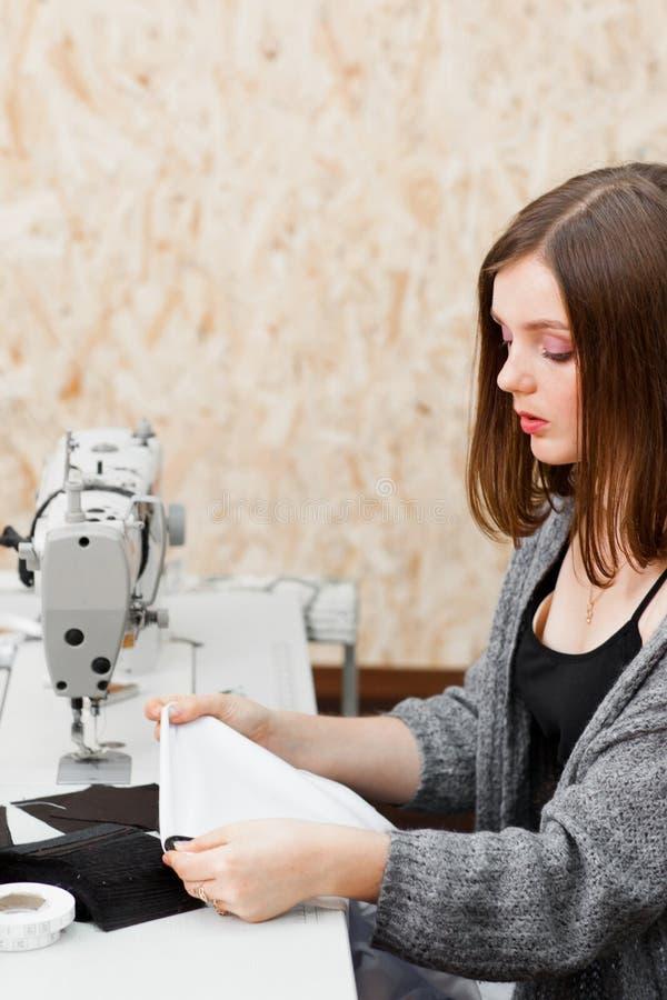Молодая белошвейка работая на студии, открытом космосе стоковое фото