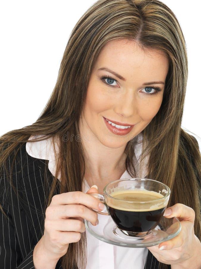 Молодая бизнес-леди выпивая чашку черного кофе стоковые фото