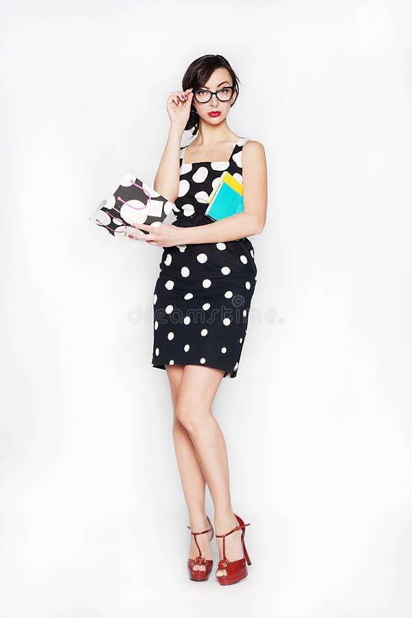 Молодая бизнес-леди в платье и стеклах с тетрадью на изолированной белой предпосылке стоковые фотографии rf