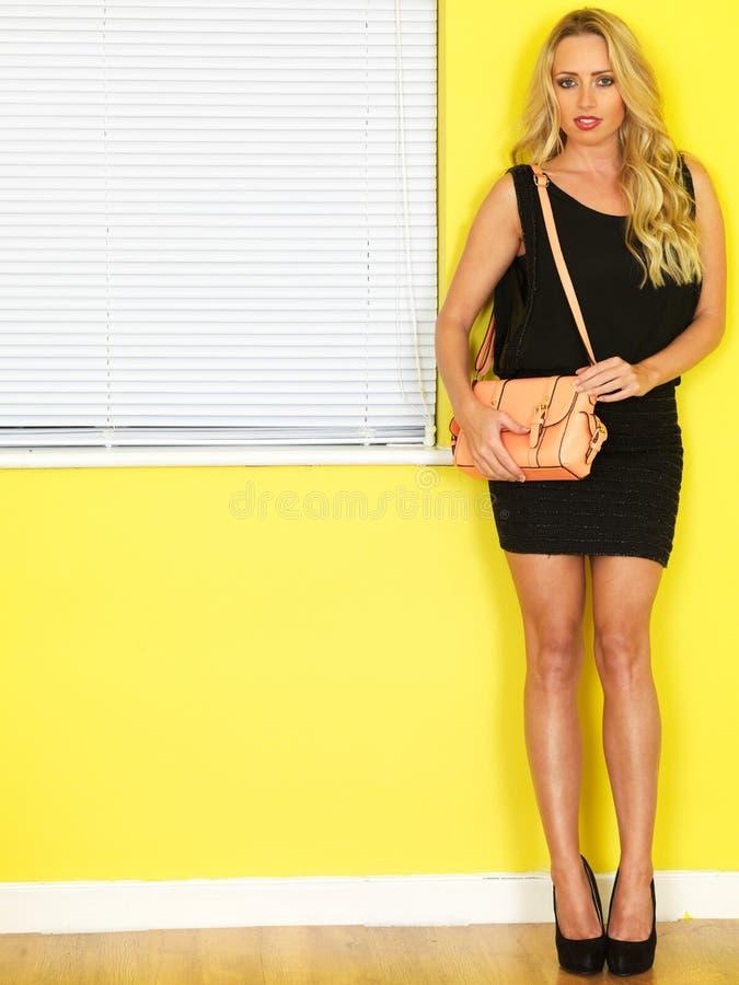 Молодая бизнес-леди держа розовую сумку нося короткое черное платье стоковая фотография rf