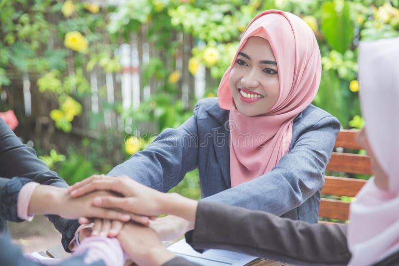Молодая бизнес-леди 4 кладя их руки совместно стоковая фотография rf