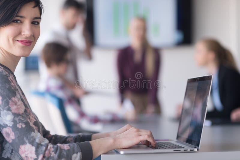 Молодая бизнес-леди на офисе работая на компьтер-книжке с командой на мне стоковая фотография rf