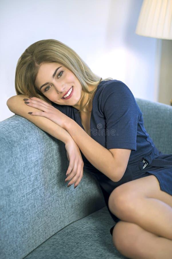 Молодая бизнес-леди ослабляя на софе после работы стоковые изображения rf