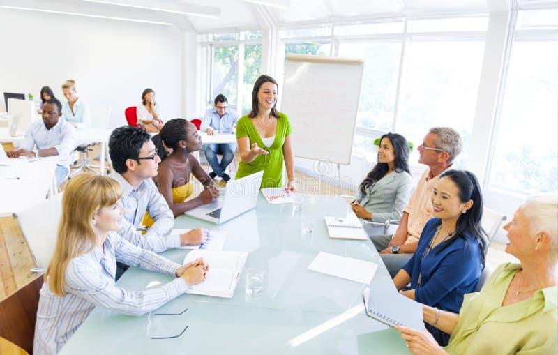 Молодая бизнес-леди представляя к ее коллегам стоковое изображение