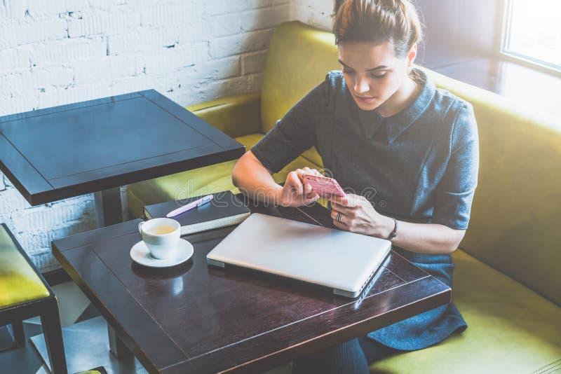 Молодая бизнес-леди сидя в кафе на таблице и smartphone пользы На таблице закрытые компьтер-книжка, тетрадь и чашка кофе стоковое изображение