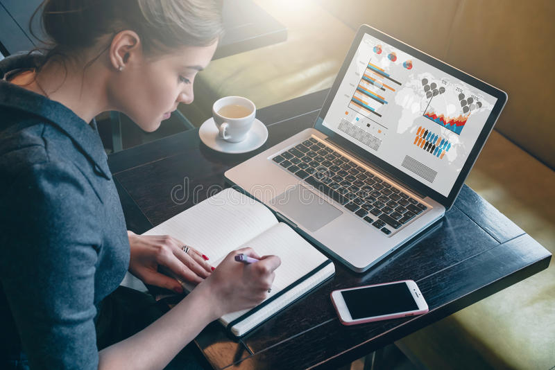 Молодая бизнес-леди сидя на таблице и принимая примечания в тетради На графиках и диаграммах экрана компьютера стоковое изображение rf