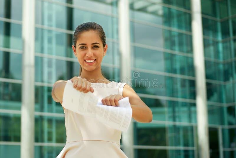 Молодая бизнес-леди срывает страницы усмехаться контракта стоковое фото