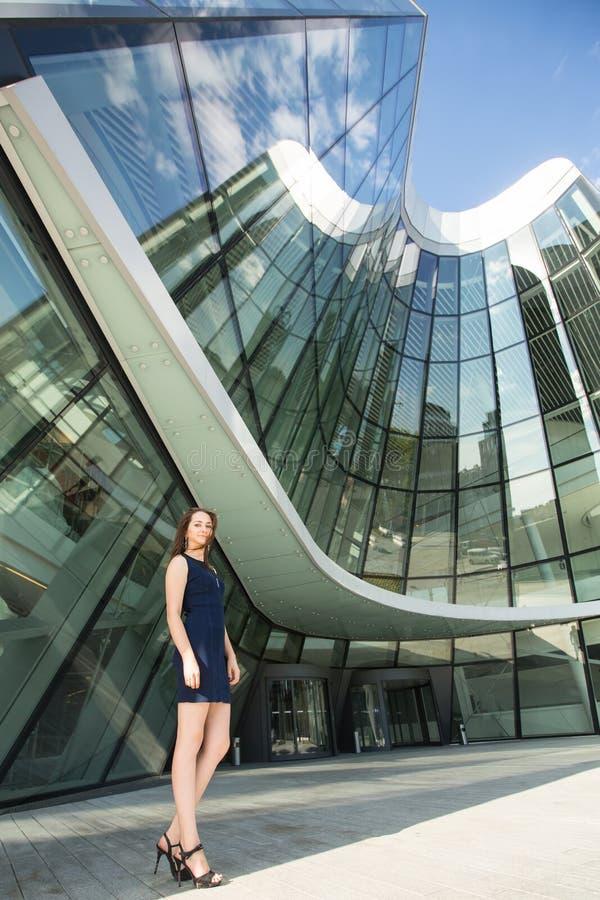 Молодая бизнес-леди стоя на заднем плане делового центра стоковые изображения